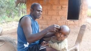 im Compound, der Vater rasiert seinem Kind die Haare ab